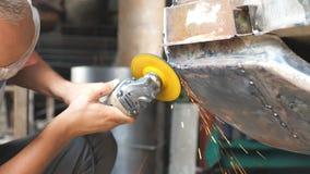 Automóvel de lustro do soldador adulto com equipamento profissional elétrico na garagem Moedura masculina do trabalhador do repar video estoque