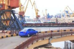 Automóvel de passageiros azul no porto no fundo dos guindastes após o descarregamento imagem de stock