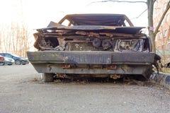 Autom?vel de passageiros queimado abandonado perto do pr?dio de apartamentos R?ssia fotos de stock royalty free