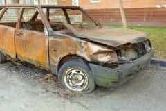 Autom?vel de passageiros queimado abandonado perto do pr?dio de apartamentos R?ssia fotos de stock