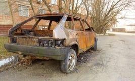 Autom?vel de passageiros queimado abandonado perto do pr?dio de apartamentos R?ssia imagens de stock royalty free