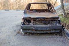 Autom?vel de passageiros queimado abandonado perto do pr?dio de apartamentos R?ssia imagens de stock
