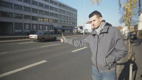 Automóvil de cogida del hombre joven en la ciudad desconocida, barato el viajar, haciendo autostop almacen de video