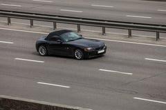 Automóvil descubierto negro de BMW z4 que apresura en la carretera vacía imágenes de archivo libres de regalías