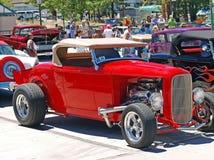 Automóvil descubierto rojo de la cómoda con patas altas Imagenes de archivo