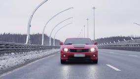 Automóvil juguetón rojo que conduce hacia cámara en la autopista almacen de metraje de vídeo