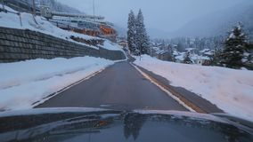 Automóvil negro con las linternas en movimientos en el camino de la montaña el día de invierno almacen de metraje de vídeo