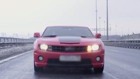 Automóvil rojo del músculo que conduce hacia cámara en la autopista metrajes