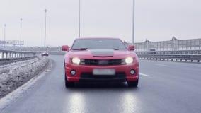 Automóvil rojo del músculo que conduce hacia cámara en la carretera almacen de video
