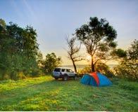Automóvil y campo en salida del sol Fotografía de archivo