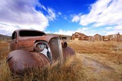 Automóvil y pueblo fantasma clásicos aherrumbrados Fotos de archivo libres de regalías