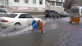 Automóviles que conducen en el camino sobre charco profundo y que salpican el agua de las ruedas