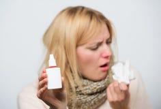 Automaatfles Ziek vrouwen bespuitend medicijn in neus Het behandelen van verkoudheid of allergisch Rhinitis Leuke vrouw stock fotografie