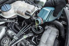 Automaster överträffar upp oljan i en bilmotor arkivbilder
