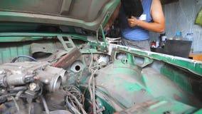 Το αρσενικό automaster ενώνει στενά τα μέρη μετάλλων του παλαιού αυτοκινήτου με τον επαγγελματικό εξοπλισμό στο γκαράζ Ενήλικος ε απόθεμα βίντεο