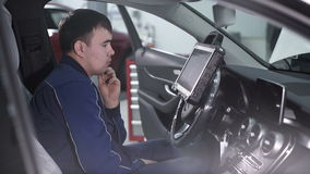 Automaster sitting in a car and thinking how to do chip tuning. The service center, mechanic in blue uniform is in the driver`s seat in the car and directly stock footage