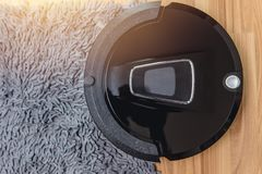 Automate Robot vacuum cleaner on laminate wood floor. With carpet cleaning machine stock photo