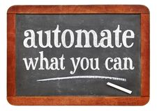 Automate what you can advice. White chalk text on a vintage slate blackboard royalty free stock image