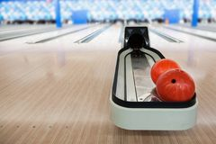 Automated Bowling Ball Return With Copy Space. Focus on foreground automated bowling ball return machine with deliberate soft background bowling alley and copy Stock Images