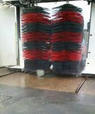 Automated car wash in France. Red and black brushes spinning with misty water spray Stock Images