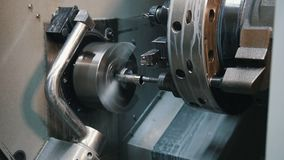 Automated lathe processes the part and creates a thread. Close up stock video footage