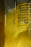 Automated Powder Coating Booth in Operation. Powder coating booth operating under standard automated conditions applying dry yellow paint electrostatically Royalty Free Stock Image