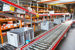 Automated warehouse. Boxes with spare parts moving on conveyer. Warehouse management system. Conveyer with automaticaly moving boxes royalty free stock images