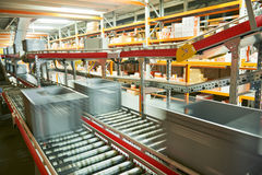 Automated warehouse. Boxes with spare parts moving on conveyer. Warehouse management system. Conveyer with automaticaly moving boxes Stock Photo