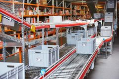 Automated warehouse. Boxes with spare parts moving on conveyer. Warehouse management system. Conveyer with automaticaly moving boxes stock photography