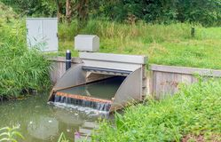 Automated working small weir in a Dutch polder ditch. Automated working small weir in a stream manages the water level in a Dutch polder. The flowing water foams stock photography