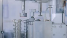 Automatic ampoule filling and sealing equipment machine at pharmacy factory. Close up - moving parts of automatic ampoule filling and sealing equipment machine stock video