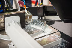 Automatic bandsaw sawing metal workpiece. Royalty Free Stock Photography