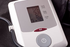 Automatic blood pressure monitor on a wooden background Stock Photography