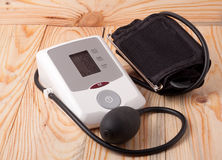 Automatic blood pressure monitor on a wooden background Stock Photos