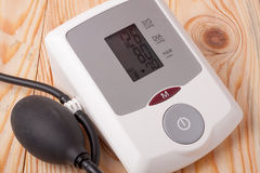 Automatic blood pressure monitor on a wooden background Royalty Free Stock Photography