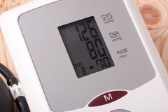 Automatic blood pressure monitor on a wooden background Royalty Free Stock Photo