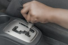 Automatic Car Gear Shift Transmission. Close up image of woman& x27;s hand holding automatic car gear shift transmission knob stock image