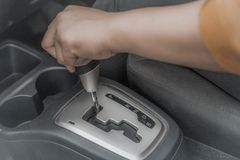 Automatic Car Gear Shift Transmission. Close up image of woman& x27;s hand holding automatic car gear shift transmission knob stock photo