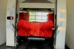 Automatic car wash. A blue SUV in an automatic car wash with big red brushes stock photo