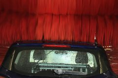 Automatic car wash. A blue SUV in an automatic car wash with big red brushes stock images