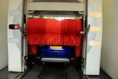 Automatic car wash. A blue SUV in an automatic car wash with big red brushes stock image