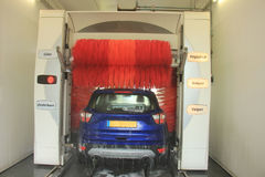 Automatic car wash. A blue SUV in an automatic car wash. Text on machine: program items in Dutch stock images