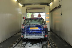 Automatic car wash. A blue SUV in an automatic car wash. Text on machine: program items in Dutch royalty free stock photo