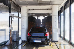 Automatic car wash service. Car being washed in an automatic vehicle wash service station royalty free stock images