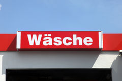 Automatic car wash. Sign in German above the entrance to an automatic car wash saying Wasche on a red background against a clear blue sky Royalty Free Stock Photography