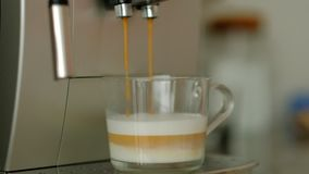 Automatic coffee machine pouring cappuccino or latte in a glass cup. slow motion.  stock video footage