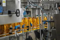 Automatic conveyor belt of production line of juice on beverage plant or factory, modern computerized industrial equipment. Fresh juice in plastic bottles stock photos