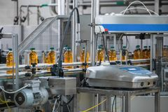 Automatic conveyor belt of production line of juice on beverage plant or factory, modern computerized industrial equipment. Fresh juice in plastic bottles royalty free stock photo