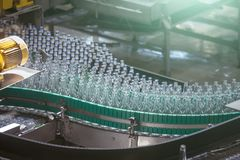 Automatic conveyor line or belt with glass bottles at brewery production. Industrial beer bottling equipment machinery. Toned stock images