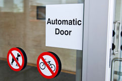 Automatic door. Sign on shopping mall entrance (dogs and bicycles are forbidden Stock Photos